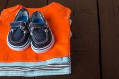 与小船鞋子的被折叠的蓝色和橙色紧身衣裤对此在木背景 新出生的男孩的尿布 堆婴儿衣物 免版税库存图片