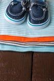 与小船鞋子的被折叠的蓝色和橙色紧身衣裤对此在木背景 新出生的男孩的尿布 堆婴儿衣物 库存图片