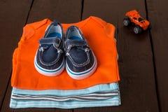 与小船鞋子的被折叠的蓝色和橙色紧身衣裤对此在木背景 新出生的男孩的尿布 堆婴儿衣物 免版税库存照片