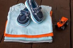 与小船鞋子的被折叠的蓝色和橙色紧身衣裤对此在木背景 新出生的男孩的尿布 堆婴儿衣物 库存照片
