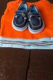 与小船鞋子的被折叠的蓝色和橙色紧身衣裤对此在木背景 新出生的男孩的尿布 堆婴儿衣物 免版税图库摄影