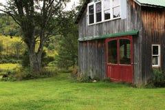与小被转换的谷仓的象草的领域有红色门和窗口的 免版税库存图片