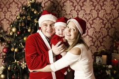 与小逗人喜爱的女婴的美丽的年轻家庭圣诞节的 库存图片