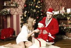 与小逗人喜爱的女婴的美丽的年轻家庭圣诞节的 免版税库存图片