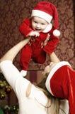 与小逗人喜爱的女婴的美丽的年轻家庭圣诞节的 免版税库存照片