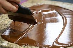 与小铲的Chocolatier搅动在花岗岩桌上的缓和液体巧克力 库存照片
