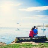 与小婴孩的家庭在海附近的一条长凳的 免版税库存照片