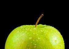 与小滴的半新鲜的绿色苹果反对黑背景的水 免版税库存照片