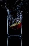与小滴的新鲜的红色苹果反对黑背景反射的水 免版税库存照片