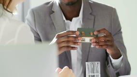 与少妇的不动产的黑代理在白色办公室举行谈判 在他的手微型房子模型 影视素材
