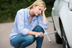 与尝试对变速轮的轮胎装卸撬杆的沮丧的母司机 免版税库存图片