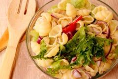 与尼奥基和菜的意大利面制色拉在一个玻璃碗服务 图库摄影