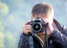 与尼康DSLR照相机的人射击 免版税库存照片