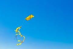 与尾巴的五颜六色的风筝在蓝天 免版税库存图片