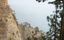 与层型结构的岩石峭壁反对雾 免版税库存图片