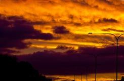 与层状云彩的金黄火热的日落 免版税库存照片