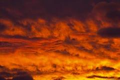 与层状云彩的金黄火热的日落 库存照片