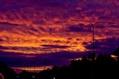 与层状云彩的金黄紫色火热的日落 免版税库存照片