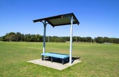 与屋顶的公园长椅 免版税库存图片