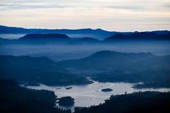 与山、湖和早晨雾的蓝色风景 多云sunrice 免版税库存照片