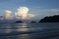 与山和云彩的海景 免版税库存图片