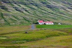 与山和住宅的冰岛自然风景 免版税库存照片