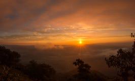 与山和海薄雾风景的日出 免版税库存图片