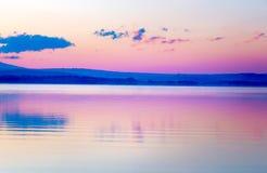 与山和湖的美好的风景在金黄,蓝色和紫色口气的黎明 库存照片