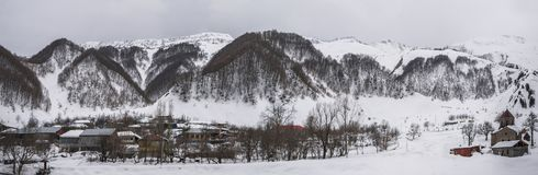 与山和老村庄的冬天风景 免版税库存图片