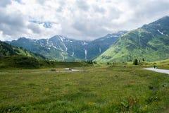 与山和草土地的风景 免版税图库摄影