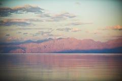 与山和风平浪静的美好的风景 免版税库存照片