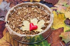 与山核桃果、核桃和红色心脏的乳脂状的焦糖蛋糕 图库摄影