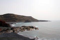 与山的黑海滩在兰萨罗特岛海岛上 库存照片