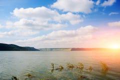 与山,绿色森林,与云彩的明亮的晴朗的天空的美好的湖风景 免版税库存图片