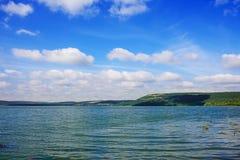 与山,绿色森林,明亮和晴朗的天空的美好的湖风景与云彩 免版税图库摄影