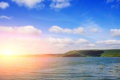 与山,绿色森林,明亮和晴朗的天空的美好的湖风景与云彩 免版税库存照片