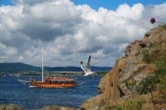 与岩石、天空、海鸥和小船的海风景 免版税库存照片