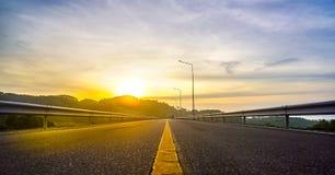?? 与岩石、晴朗的天空与云彩和美丽的柏油路的风景在晚上 免版税图库摄影