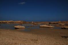 与岩石和一个人的海滩 库存图片