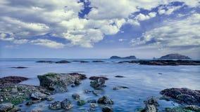 与岩石和剧烈的云彩,大连,中国的海滨 库存照片