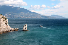 与岩石和峭壁的风景海视图。船航行。 免版税库存照片
