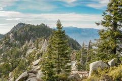 与岩石和树的山土坎以及山在背景中 免版税库存照片