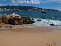 与岩石和沙子海滩的阿卡普尔科海湾 库存照片