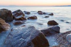 与岩石和波浪的风景在日落 库存照片