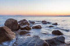 与岩石和波浪的风景在日落 免版税库存图片