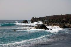 与岩石和波浪的黑沙子海滩 免版税库存图片