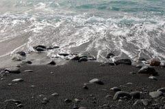 与岩石和波浪的黑沙子海滩 图库摄影