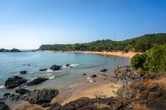 与岩石和蓝色海的海滩 库存照片