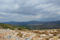 与岩石在forefround和有些山羊的谷在多云天 库存照片