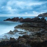 与岩石海岸线和长前的惊人的风景黎明日出 免版税库存图片